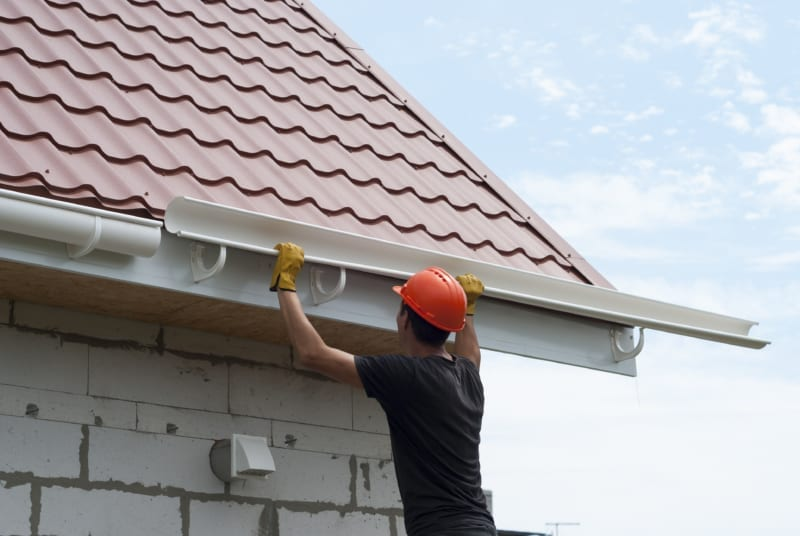 worker installing the gutter system on the roof