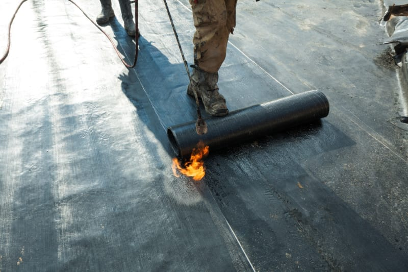 contractor unrolling roofing on a new flat roof