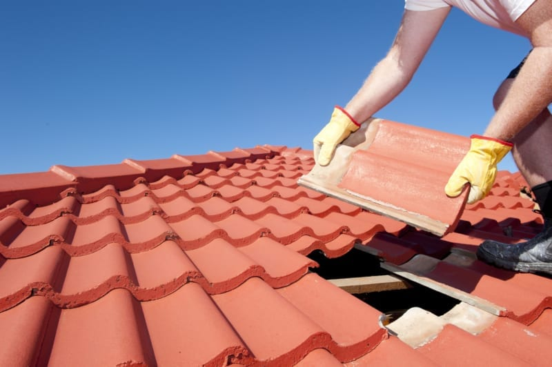 worker working on a roof to replace a tile