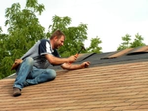 contractor in jeans working on roof replacement, nailing shingles