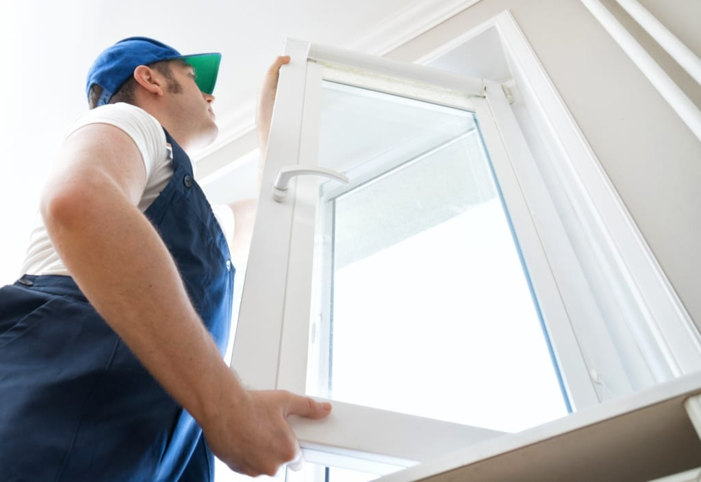 Professional handyman installing windows in a home.